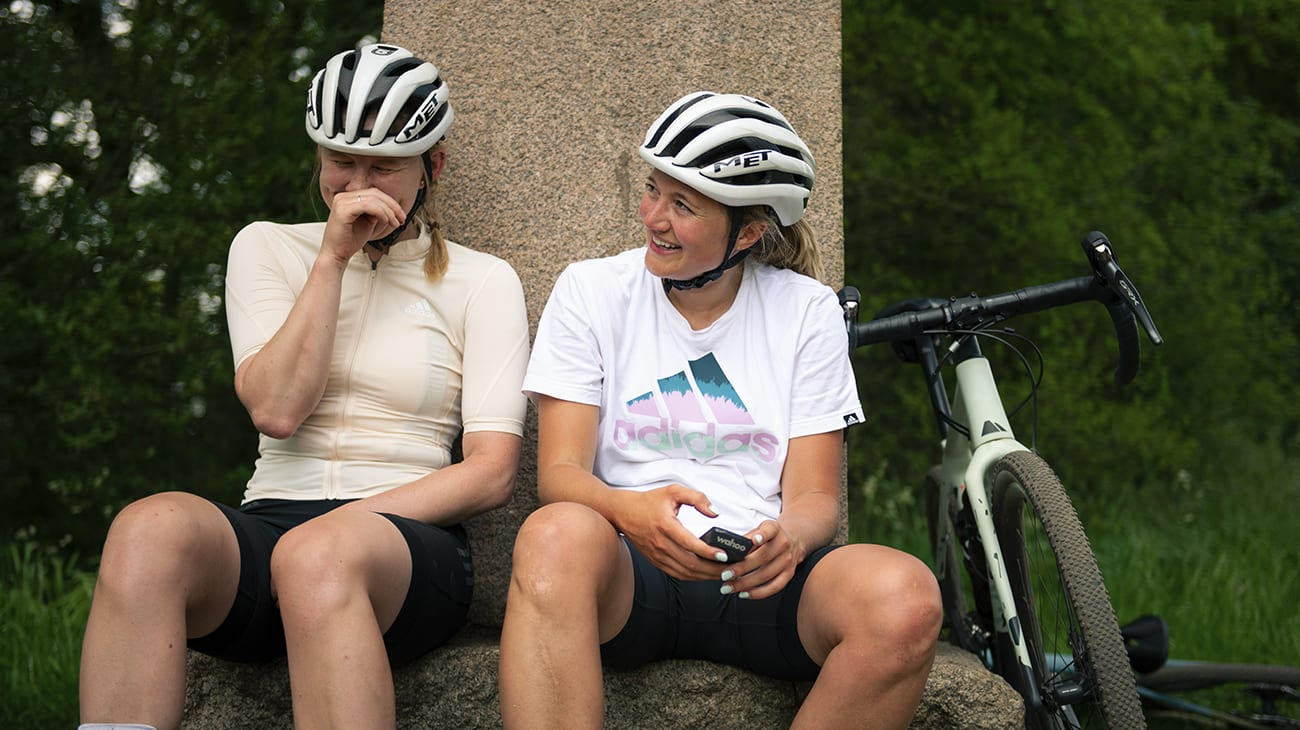Two women wearing cycling apparel laugh after summiting a climb