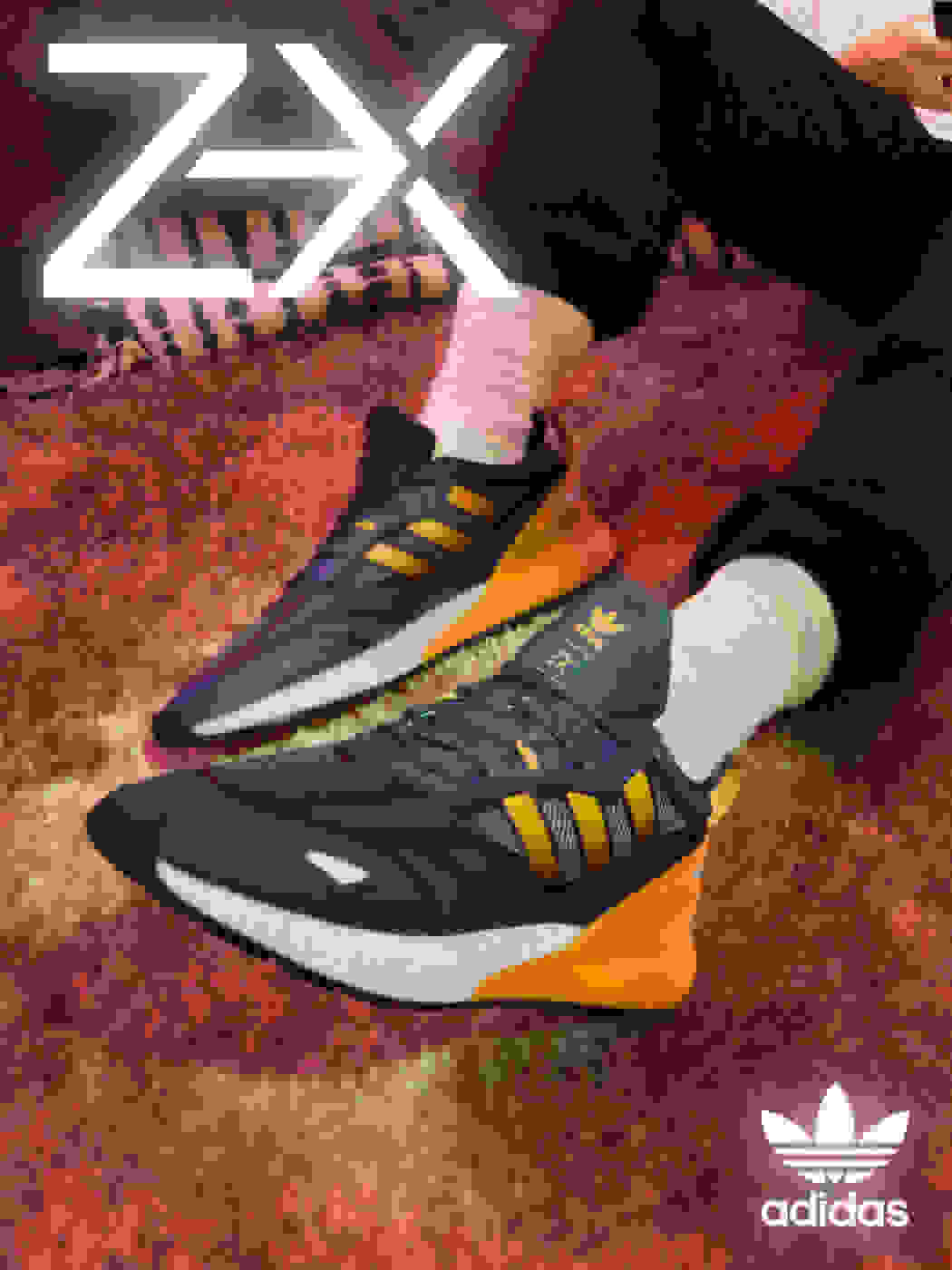 A model lounges on the carpet in front of a laptop wearing the ZX 2K Boost 2.0 with orange glow-inspired highlights on the heel and stripes.