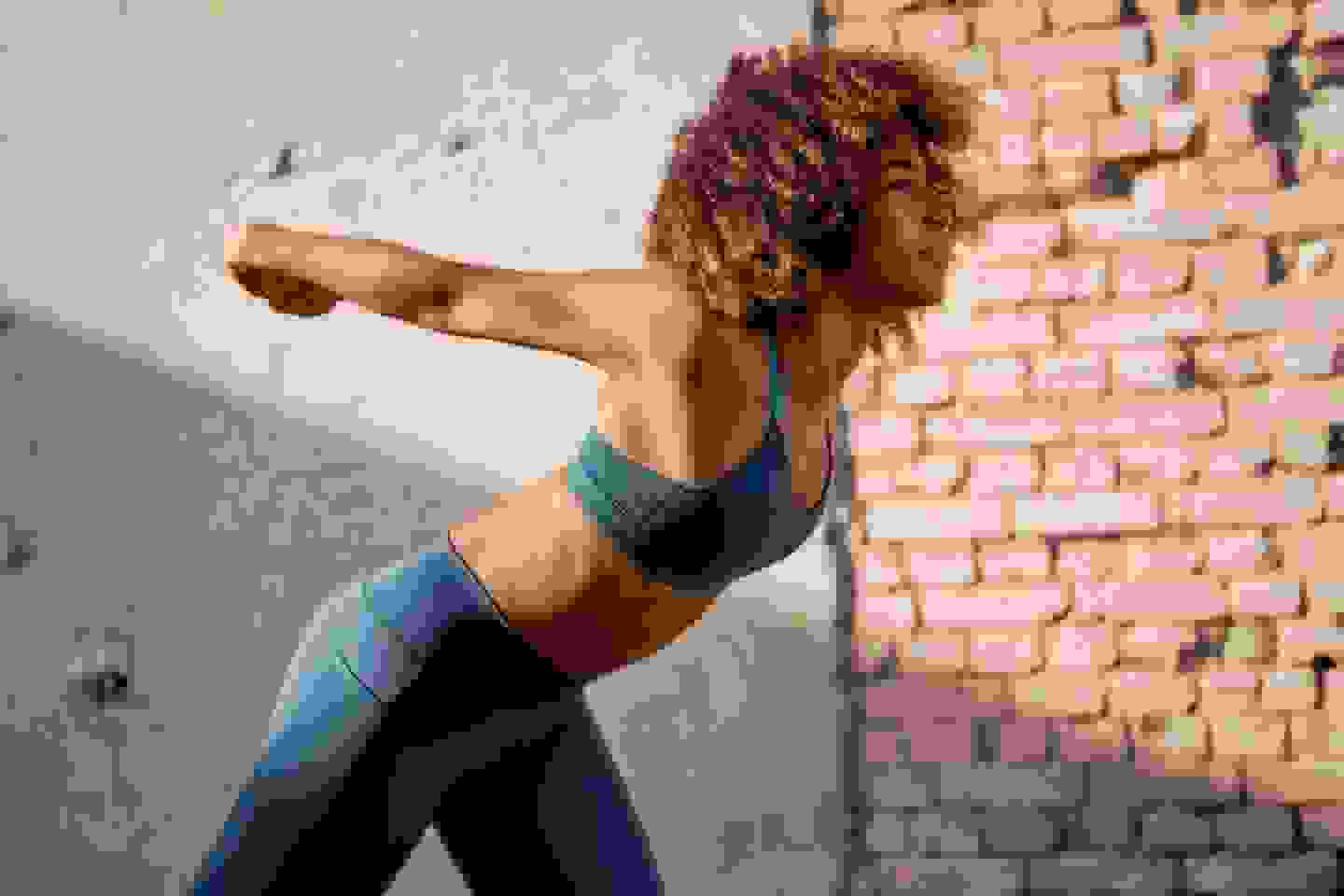 A close-up of a woman wearing an adidas bra and arching her back in front of a concrete wall.