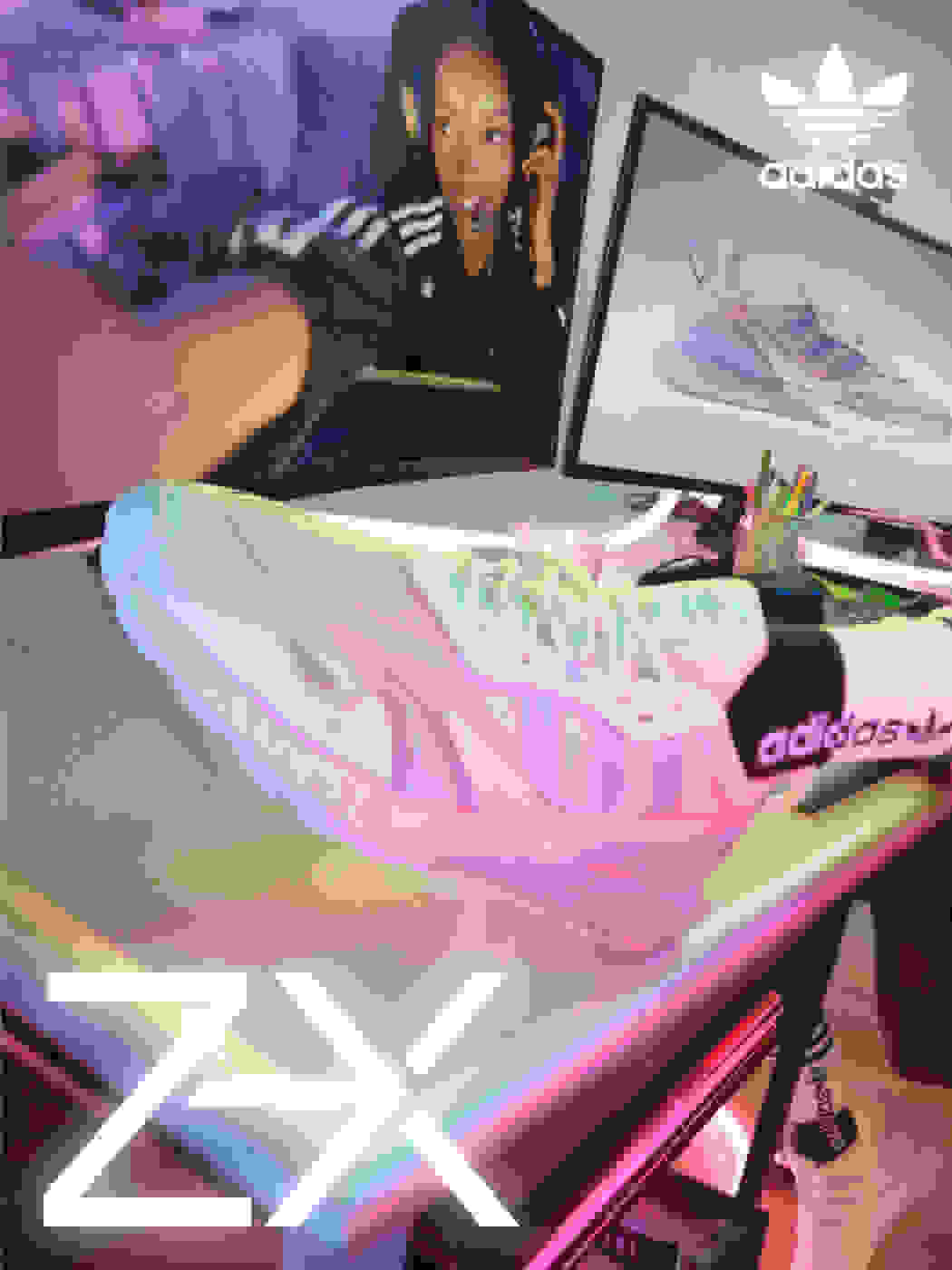 A model sits in front of a monitor where the white ZX 2K Boost 2.0 shoe with baby pink highlights on the heel and Three Stripes is shown.