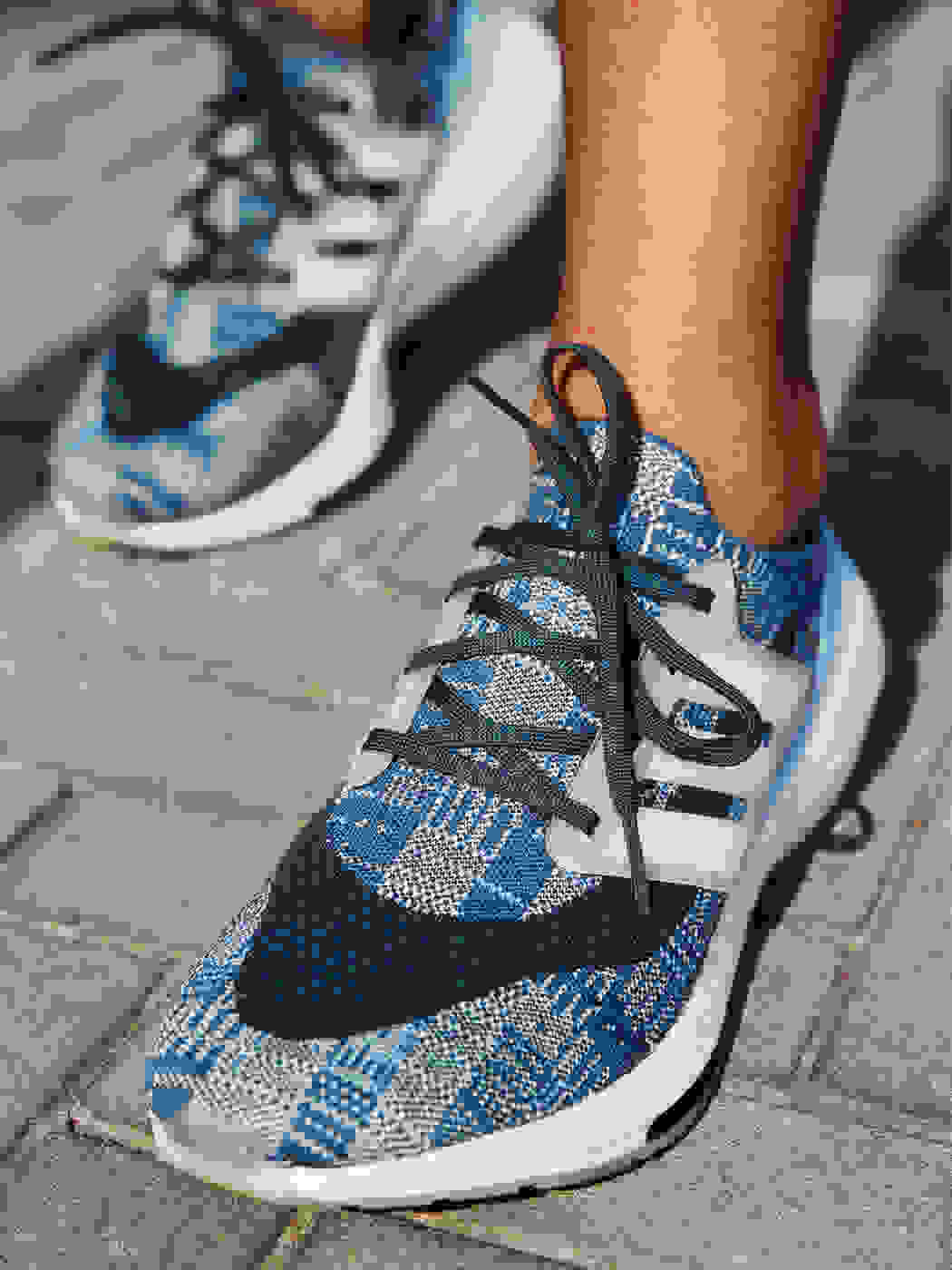 A person is wearing Primeblue Ultraboost 21 running shoes