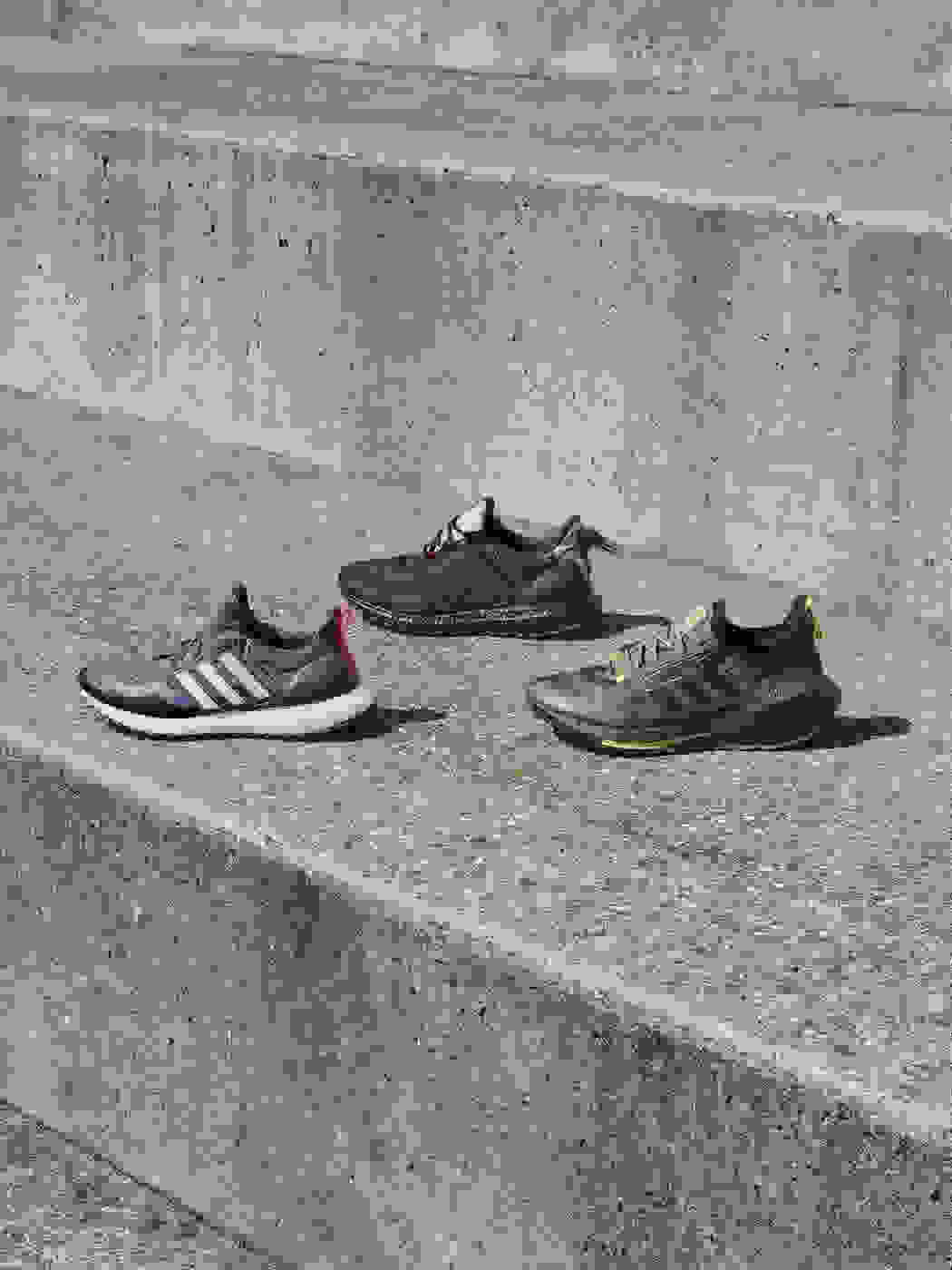 Four singular Boost trainers displayed on outdoor sports centre steps.