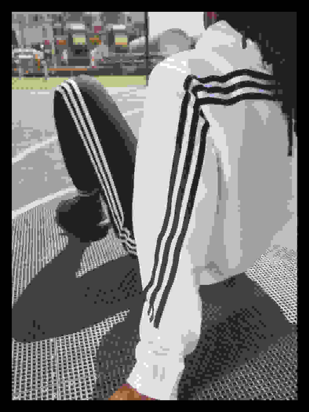 A woman sits on a basketball court, her back to the camera. She wears a white adidas top and black adidas bottoms.