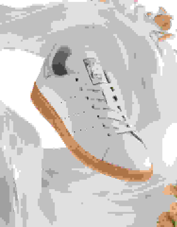 Pair of Stan Smith Mylo on a white background. Around the shoes are materials and elements part of the construction process.