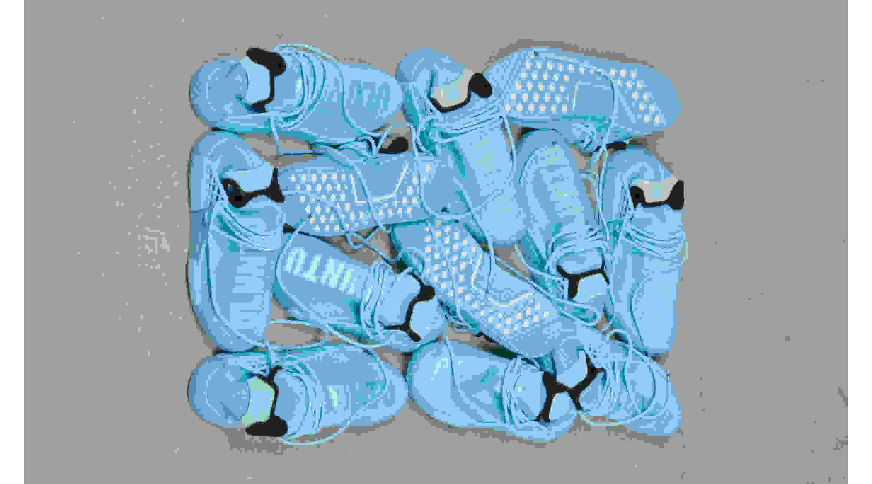 An overhead shot of a jumble of twelve bright blue HU NMD shoes, showcasing the silhouette's Primeknit upper and textured outsole.