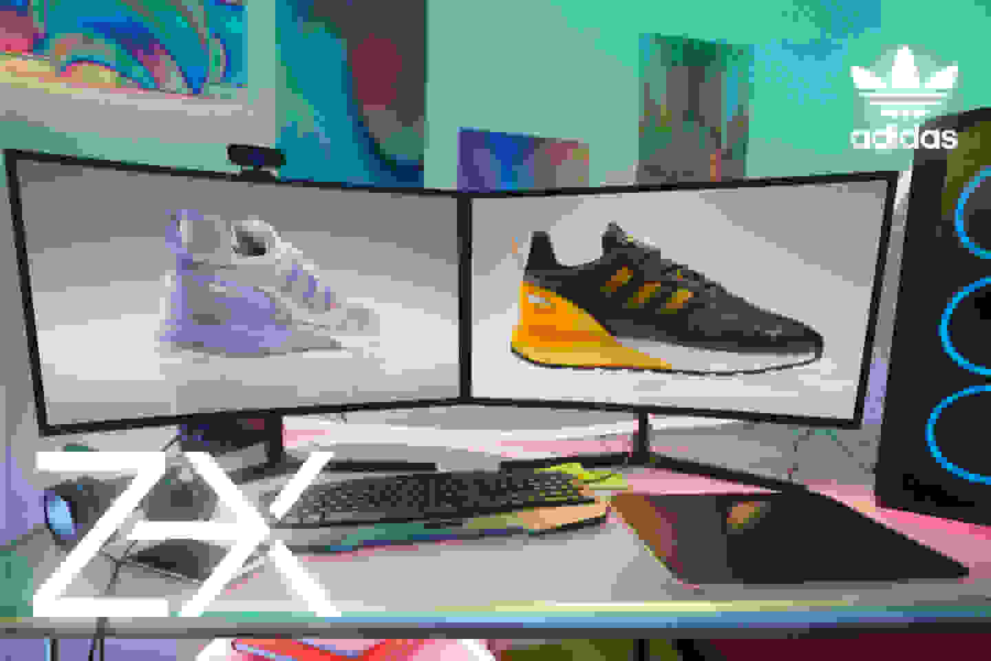 Two ZX 2K Boost 2.0 shoes are seen on two large monitors with the screens' glow reflecting onto the desk.