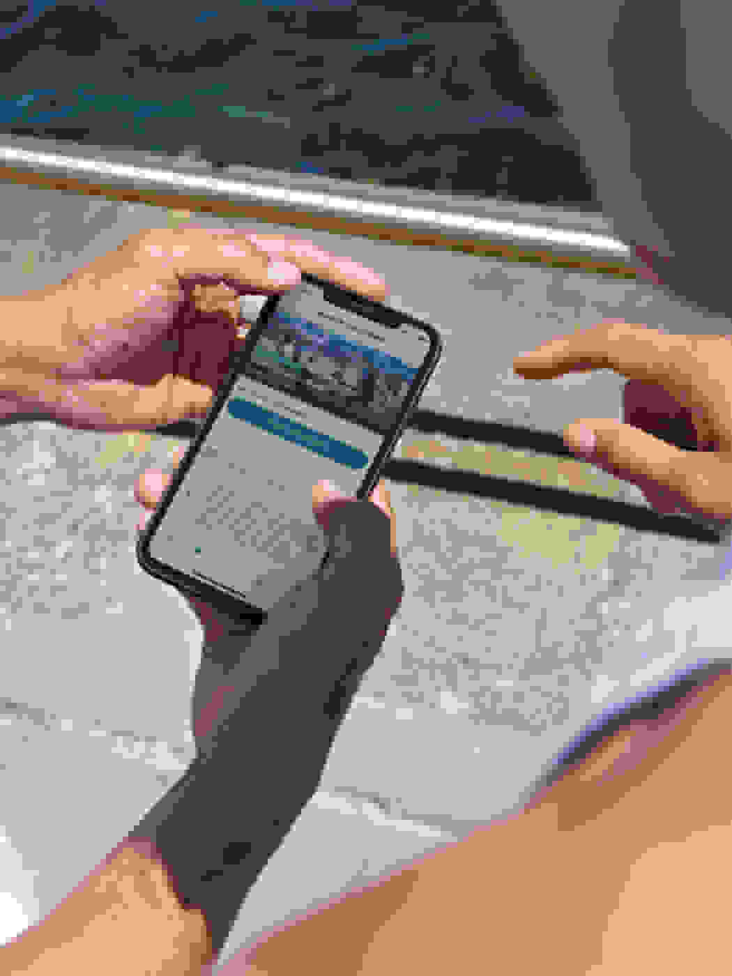 A person is holding a mobile device showing the adidas Running app on screen