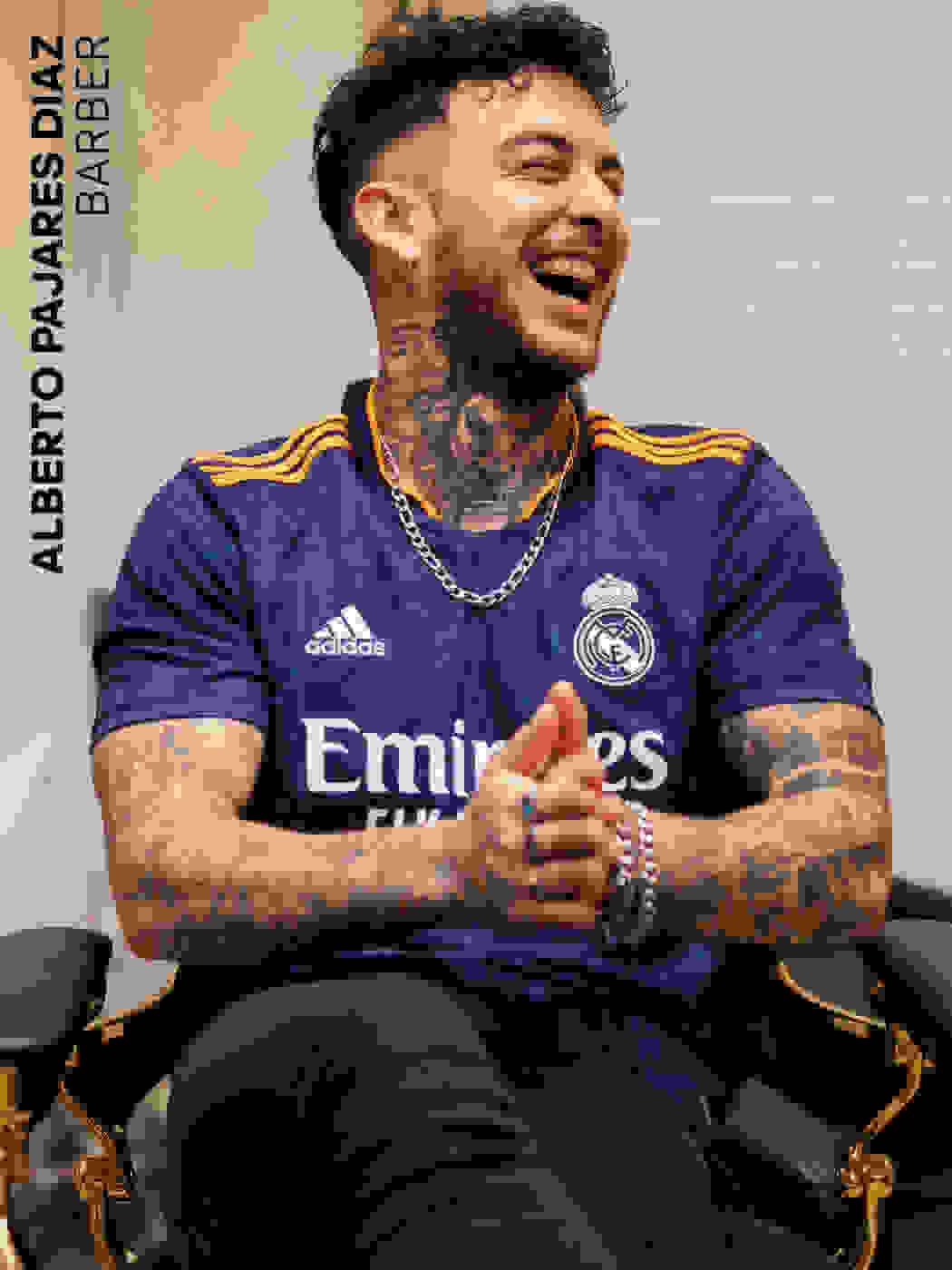 A male fan wearing a Real Madrid Away Jersey in a shop