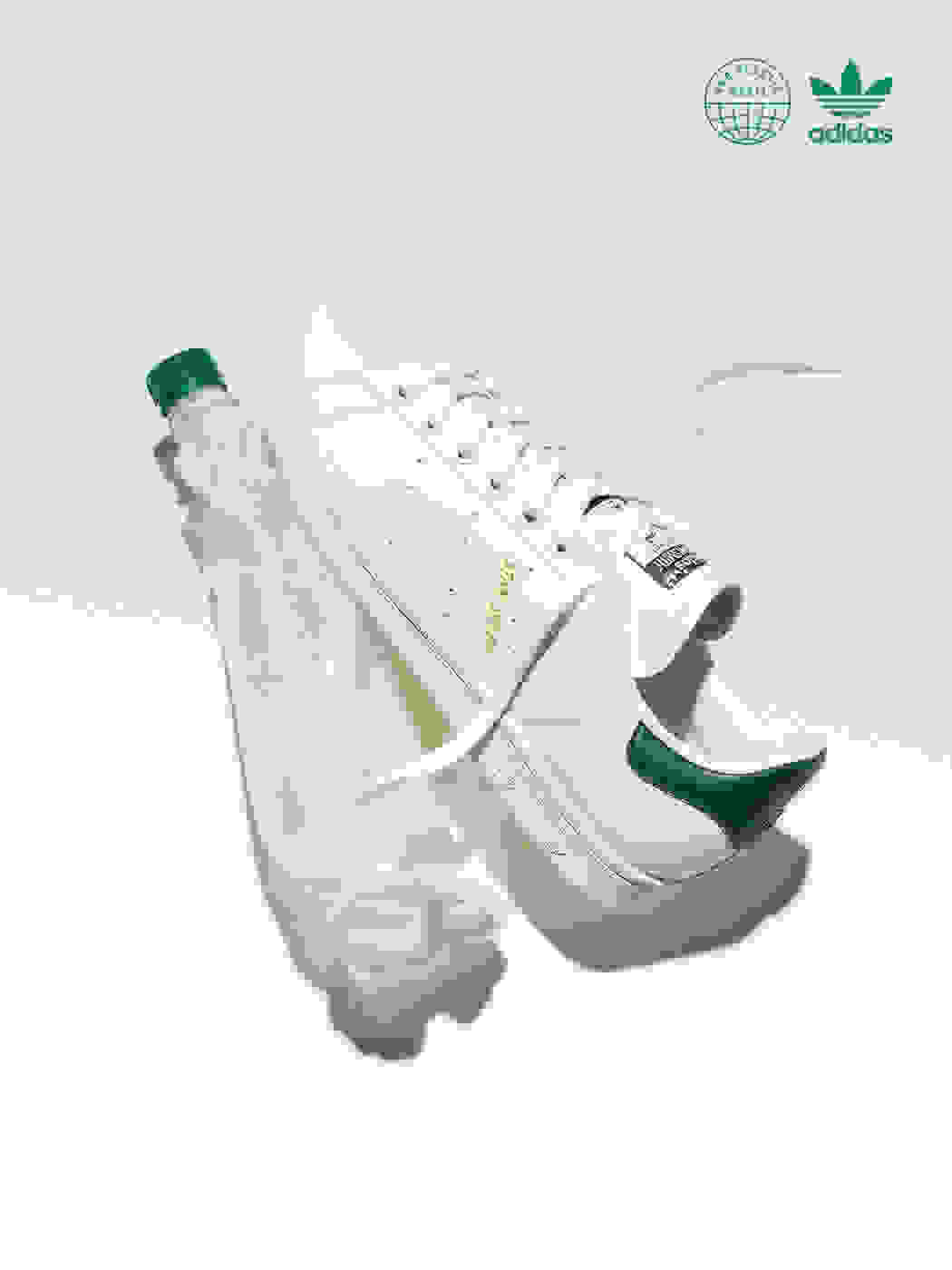 Stan Smith shoes next to a crumpled water bottle on a white background.