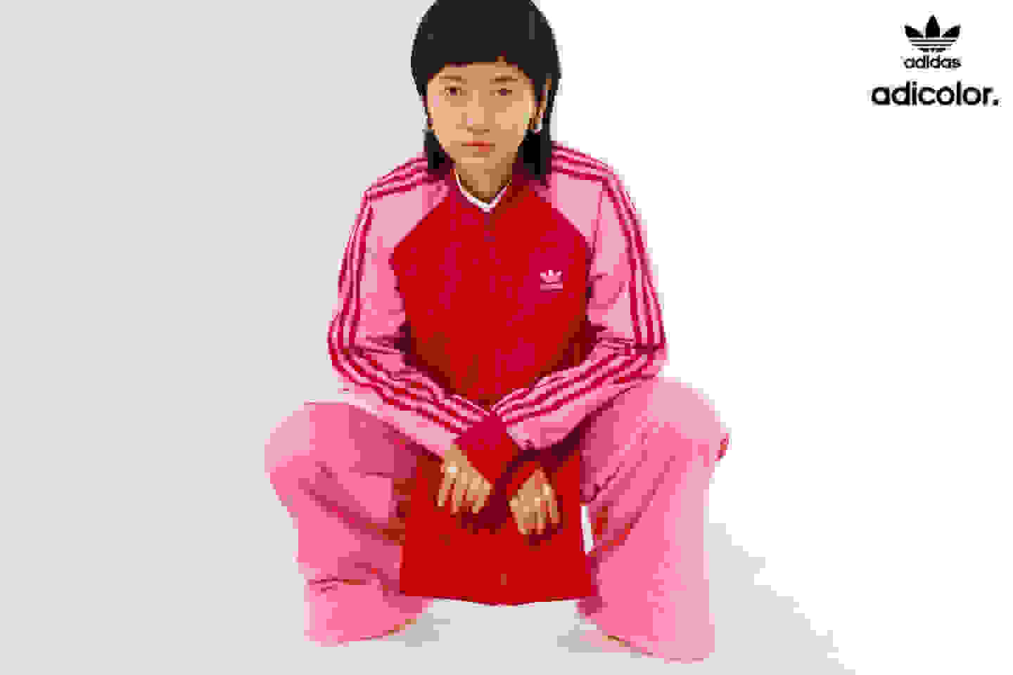 Stylish woman wearing classic red and pink adicolor tracksuit