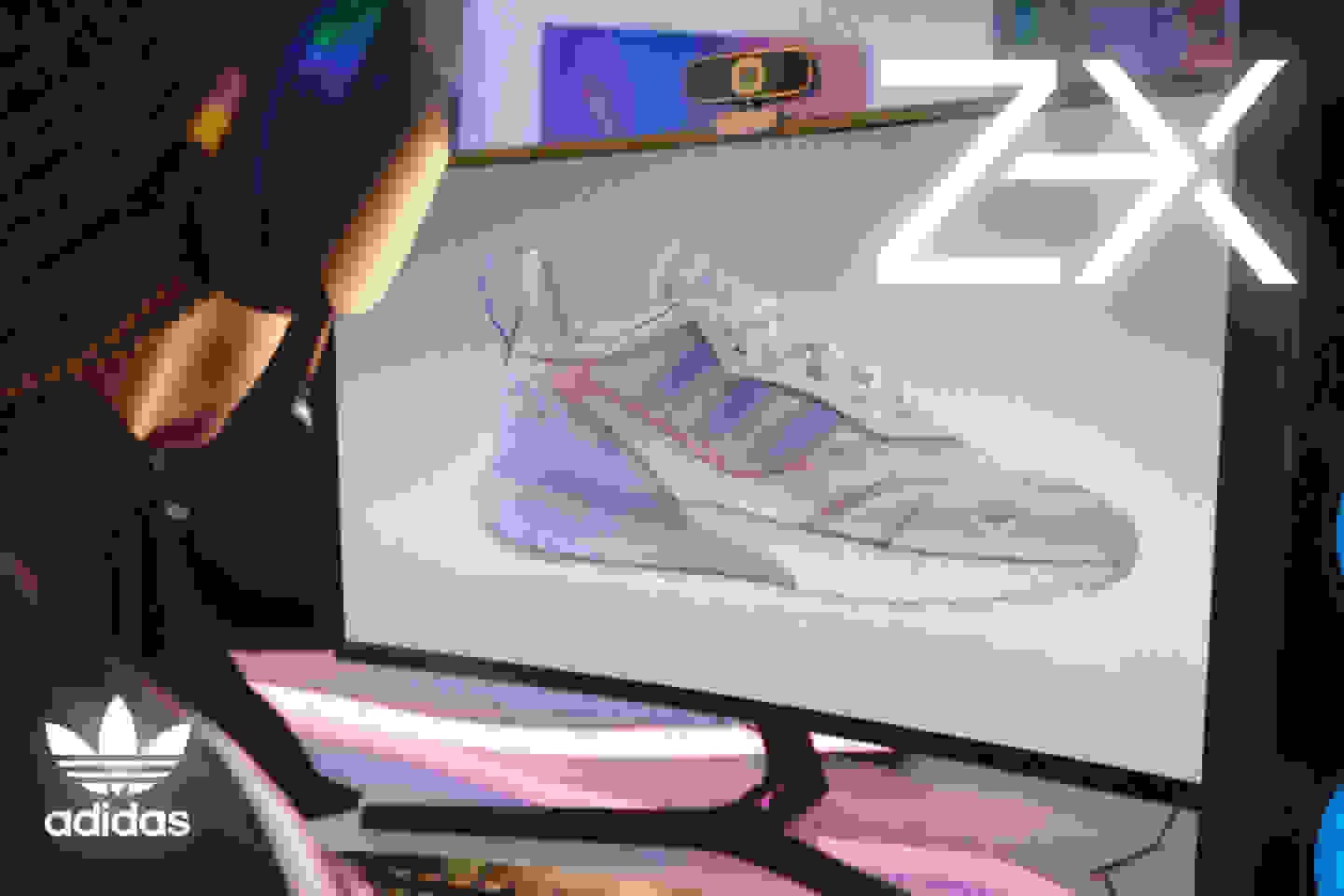 A model sits in front of a large monitor showing a sideview of the white ZX 2K Boost 2.0 shoe with baby pink highlights.