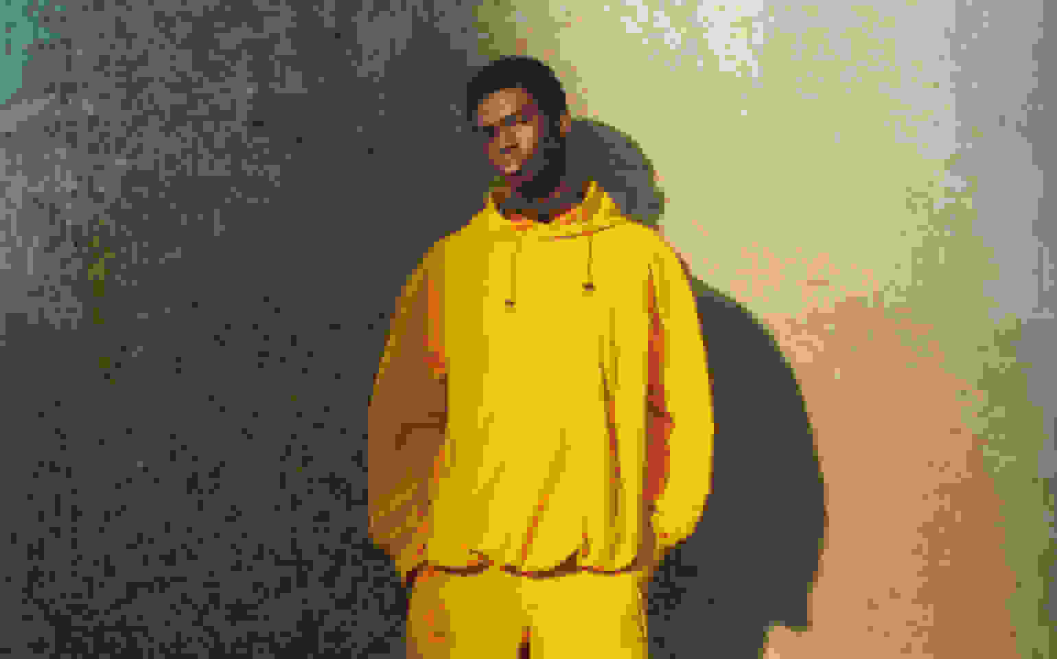 A close-up of a model leaning against a pillar, wearing a a yellow drawstring hoodie and matching shorts.