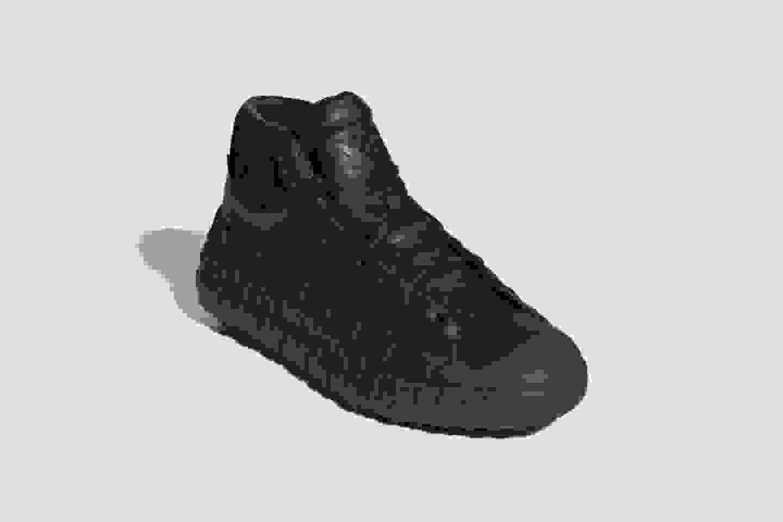A spotlight illuminates a pair of Y-3 GR.1P GTX high-top shoes.