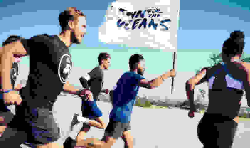 Runners running with the run for the oceans flag