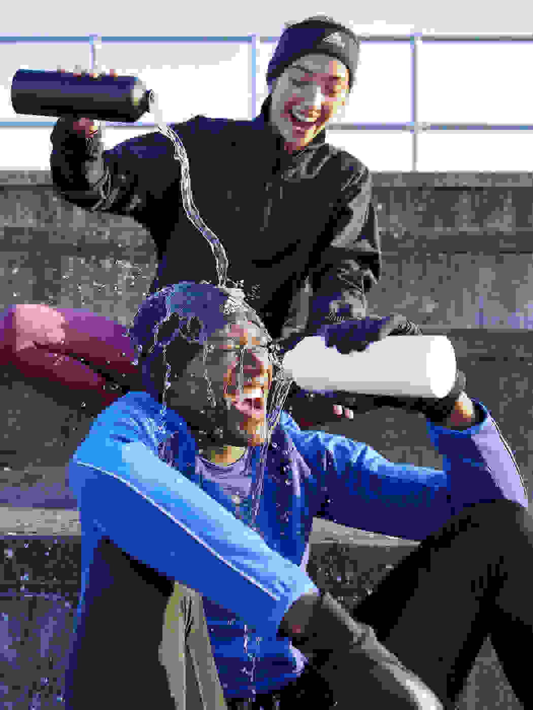 Female runner playfully pours water from a water bottle over a laughing male runner's head.