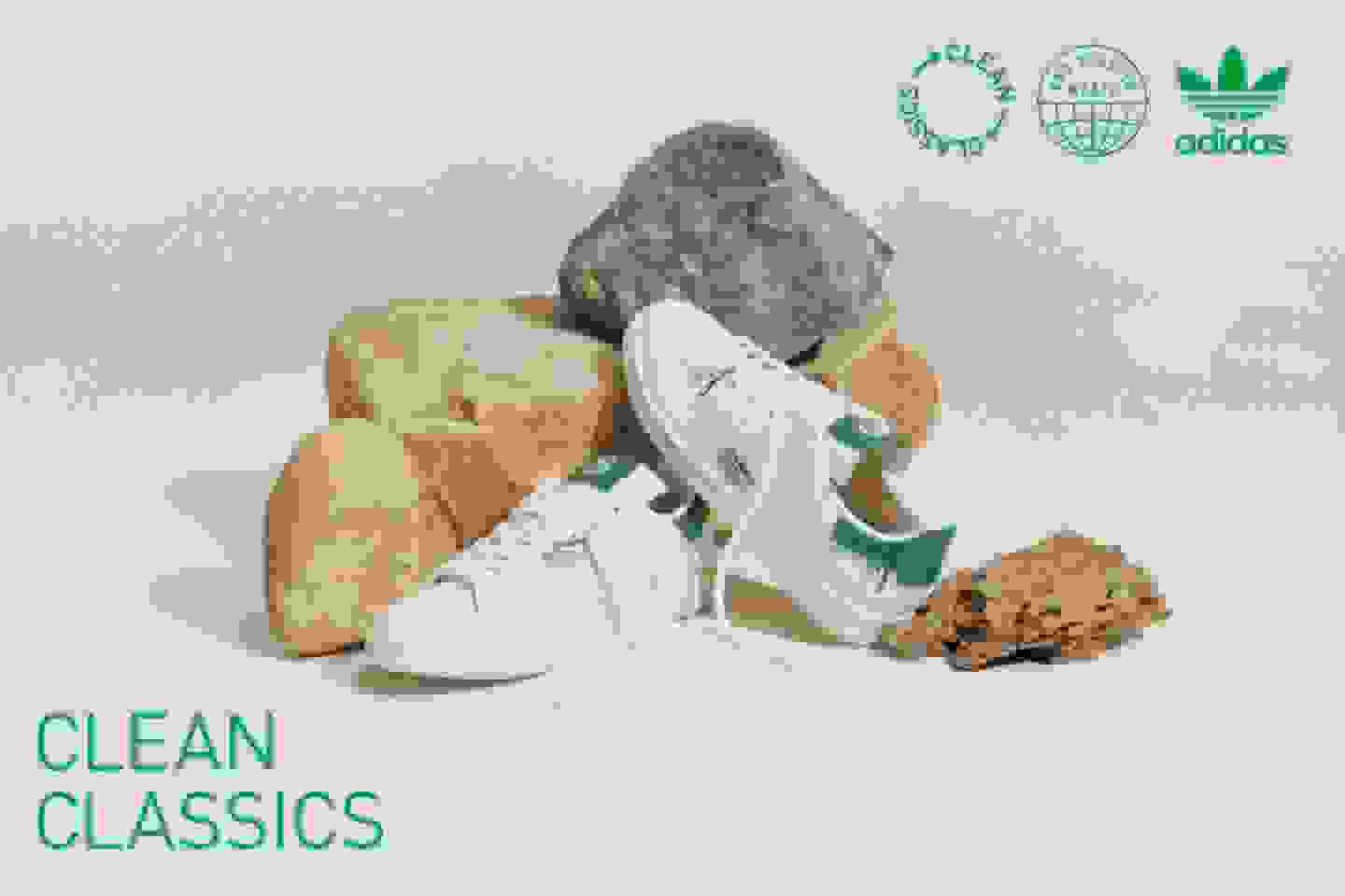 A pair of Stan Smith sneakers from the Clean Classics collection is sitting by a collection of rocks.