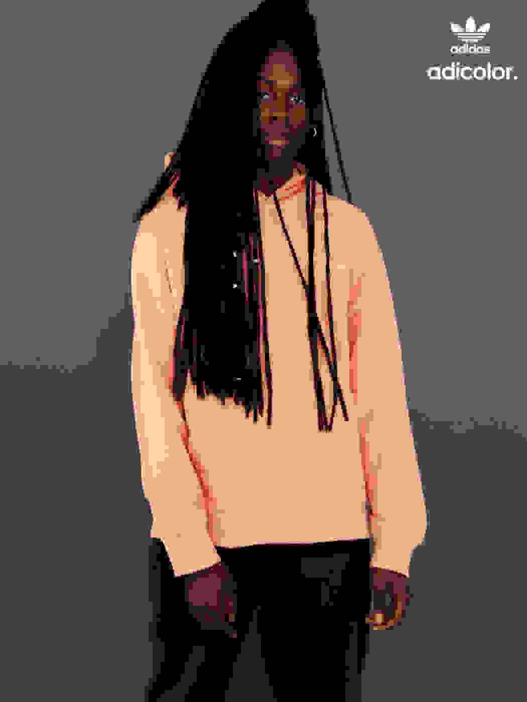 Man wearing contemporary pastel colored hooded sweater and black pants