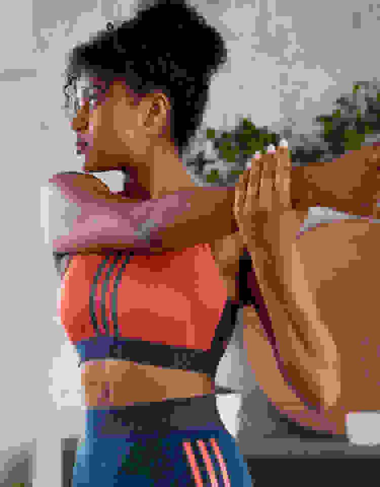 Une femme portant une brassière adidas rouge regarde par-dessus son épaule pendant qu'elle étire son bras.