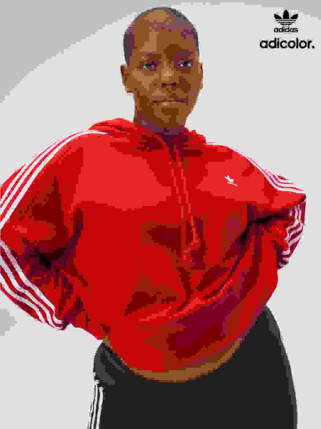 Stylish woman poses in scarlet adicolor hoodie, black shorts