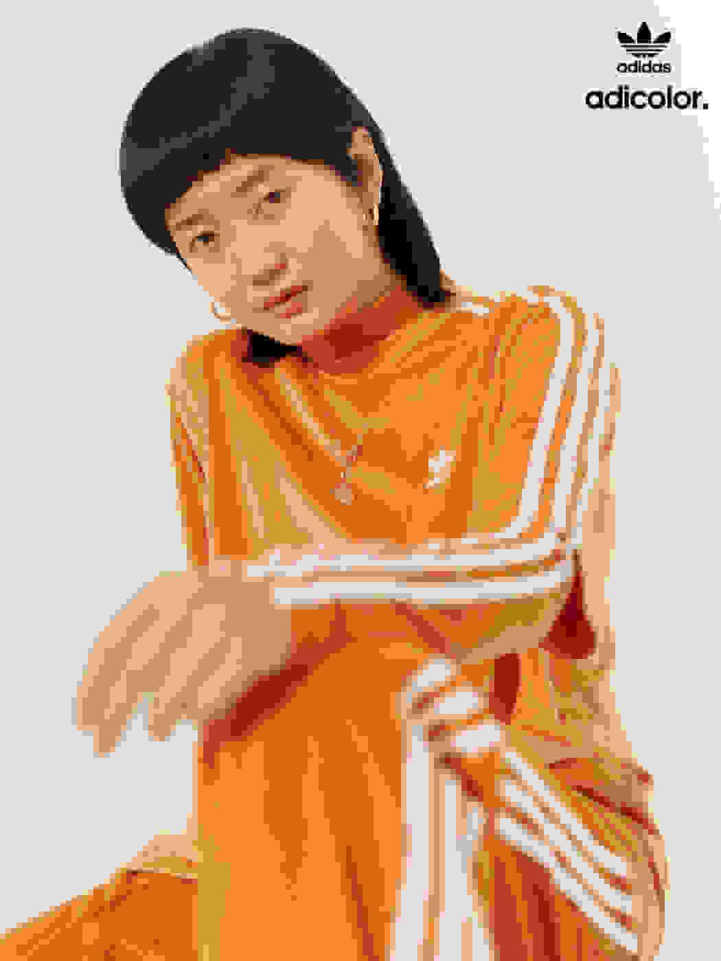Stylish woman wearing classic orange adicolor outfit.