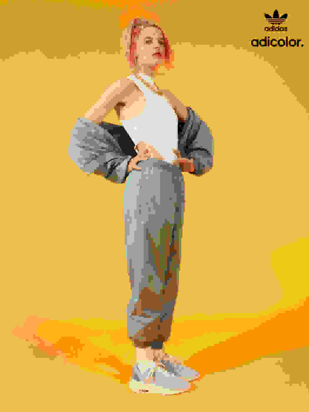 Expressive woman poses in bold light grey adicolor tracksuit.