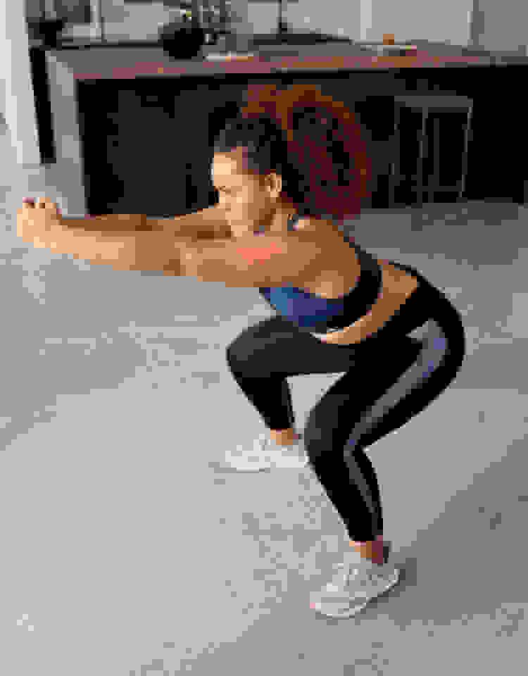 Een vrouw in een blauwe beha en een zwarte legging kijkt vooruit als ze een squat uitvoert.