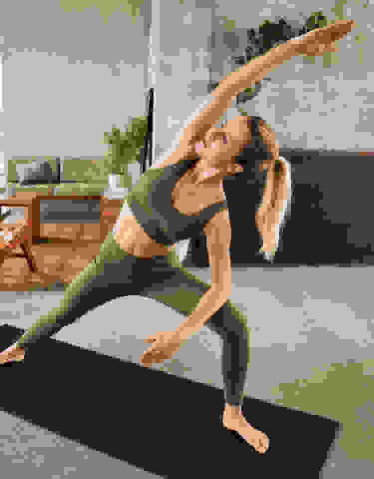 Een vrouw in een olijfgroene beha en legging rekt op een mat in haar woonkamer.