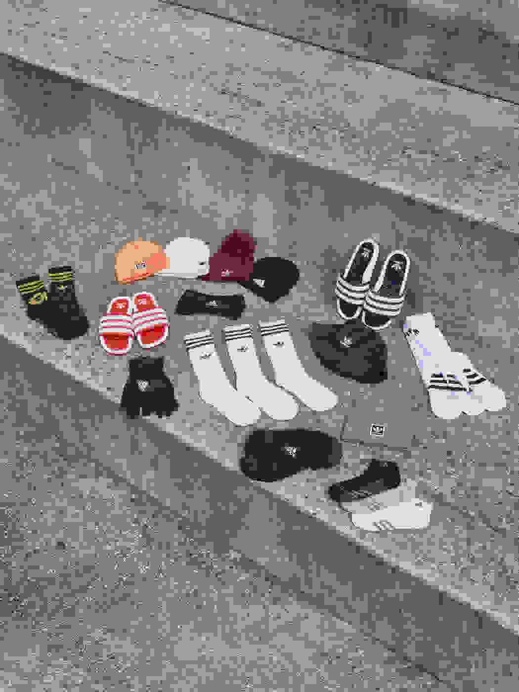 Three pairs of gloves and a beanie hat displayed together on a grass football field.