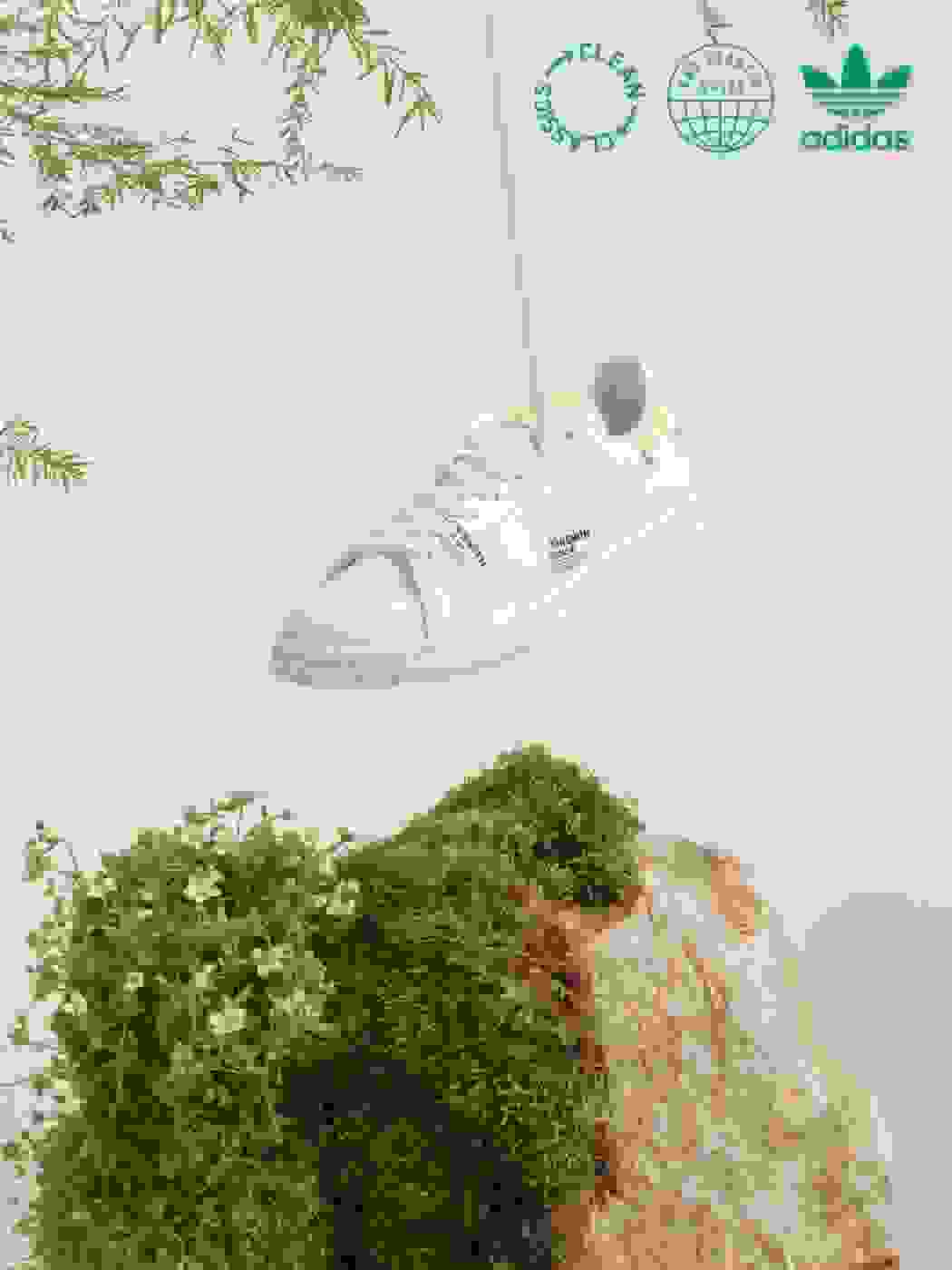 A Stan Smith sneaker from the Clean Classics collection is suspended from the ceiling and dangling above a mossy stone.