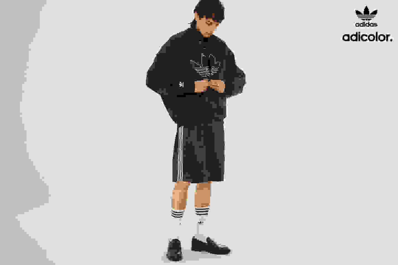 Stylish man poses in classic black adicolor jacket with shorts