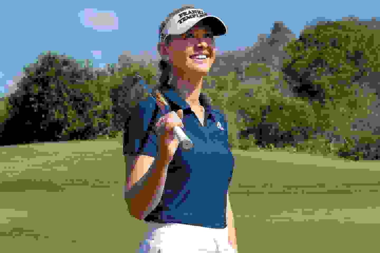 woman playing golf wearing a polo