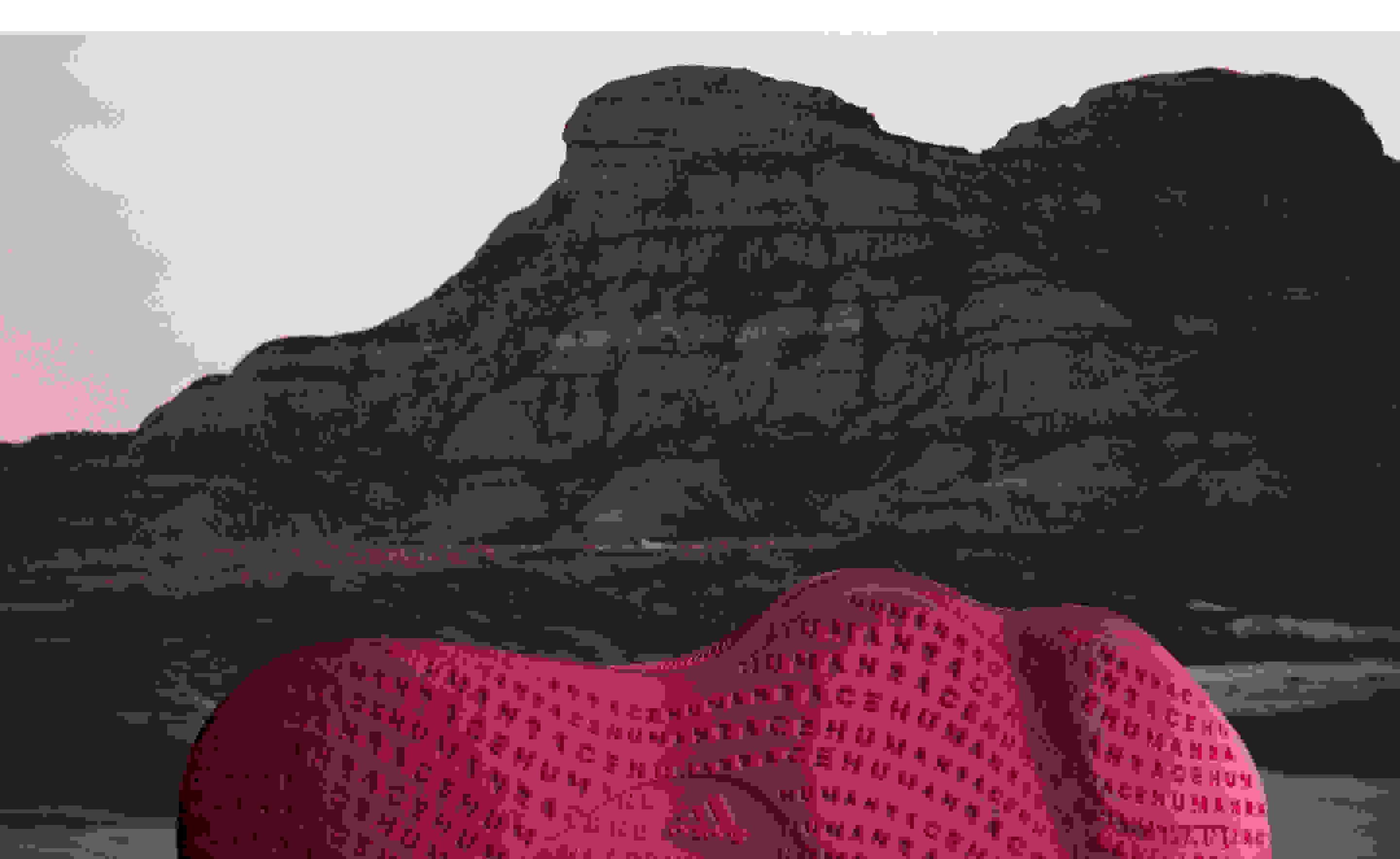 The outsole of a burgundy Humanrace Sičhona shoe against the backdrop of a mountain and tinted sky.