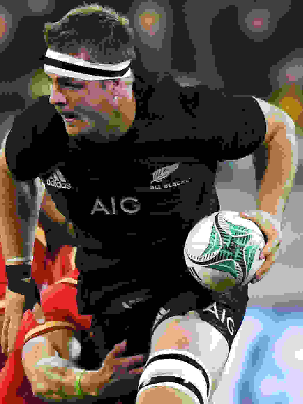 Sam Cane of All Blacks, driving forward with the ball in a match.