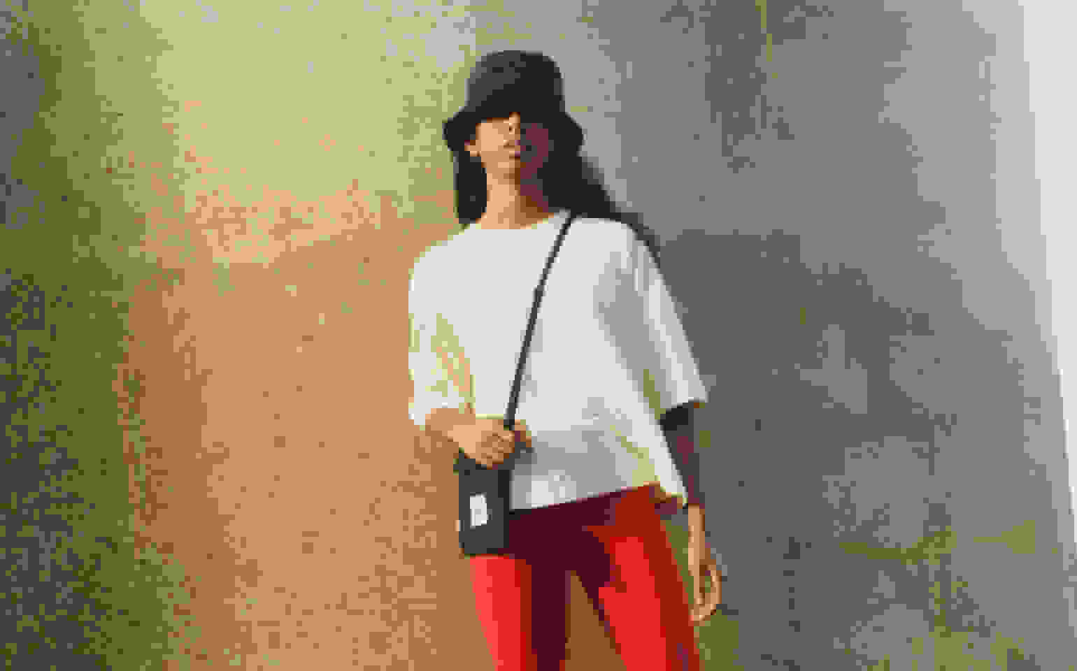 A model stands in front of a bridge pillar, wearing a black bucket hat, white top and red shorts from the Y-3 SS21 collection.