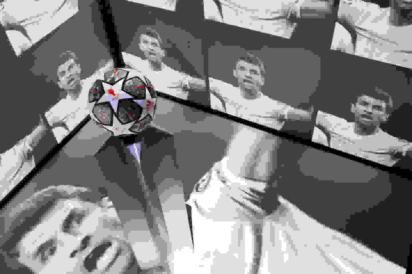 ball on plinth surrounded by screens featuring muller