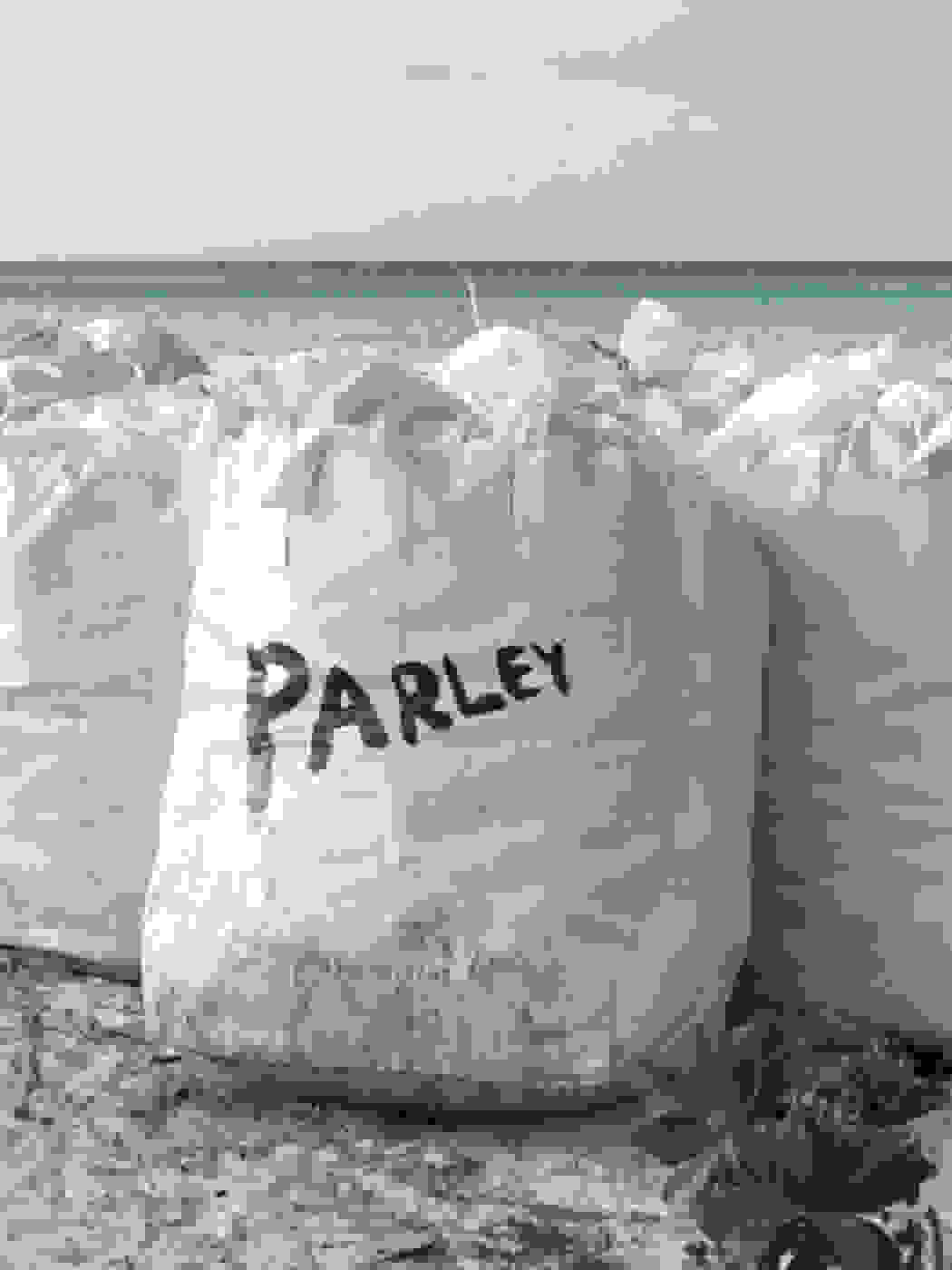 A bag with Parley logo is filled with plastic waste collected on the beach