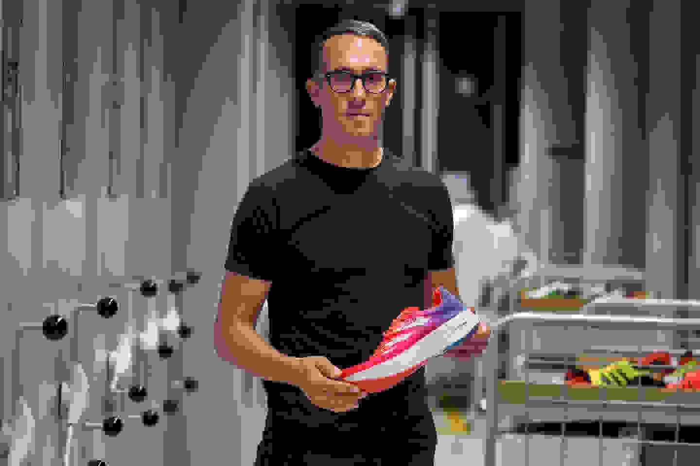 adidas design VP holding an ADIZERO running shoe