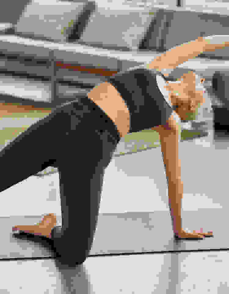 Siyah sporcu sütyeni ve taytıyla matın üzerinde yoga pozunda esneyen bir kadın.