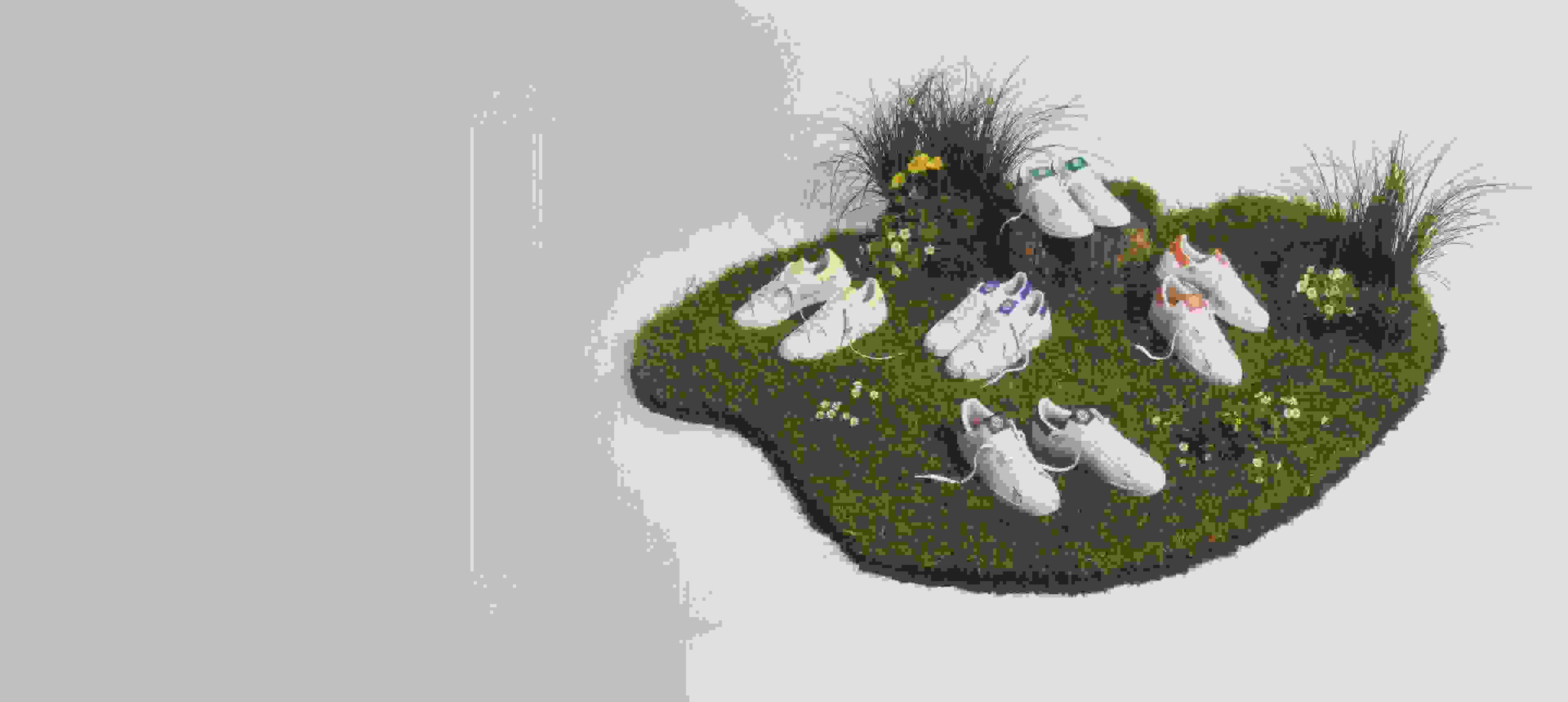 Pairs of Stan Smiths, Continental 80s, and Superstars from the Clean Classics collection on a patch of grass dotted with wildflowers.