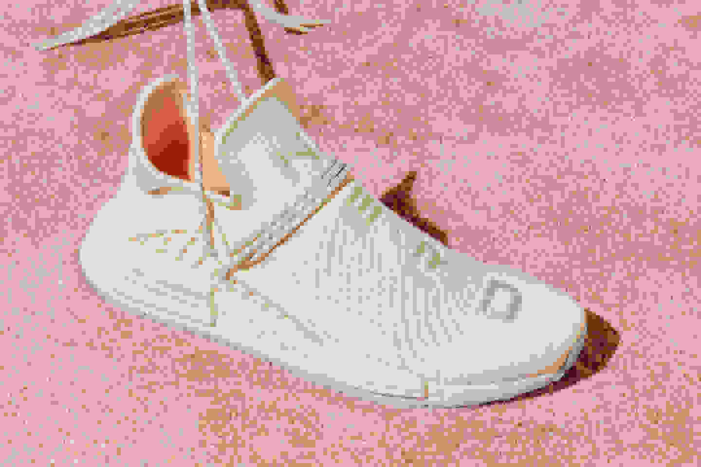 The HU NMD N.E.R.D. is set on a pink carpet. The chalk-coloured Primeknit upper, unique NMD lace-up and icy blue outsole are shown.