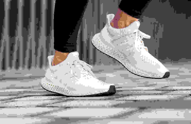 Giày chạy bộ màu trắng trên nền màu xám và trắng