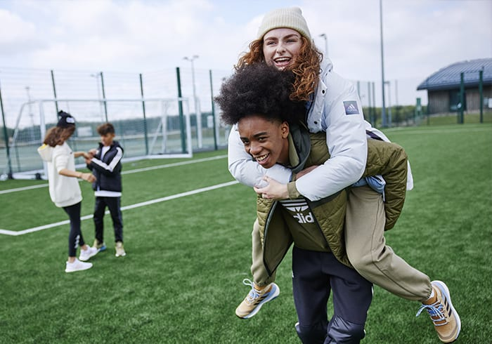 Man gives woman a piggyback ride on a sports field with two children playing in the background.