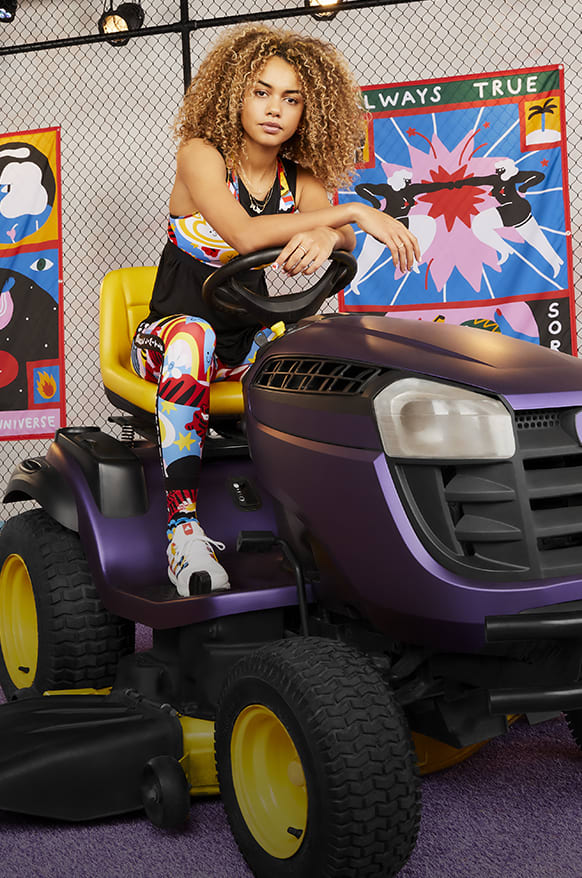 Model wearing the new Egle Sport Collection sitting on tractor in football court