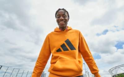 English footballer Noni Madueke smiles as he looks down at the camera, wearing an orange adidas hoody.