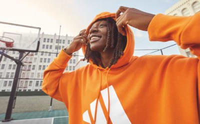 WNBA player Erica Wheeler smiles as she lifts her orange adidas hoody away from her face. She's standing on a basketball court, with city buildings behind her.