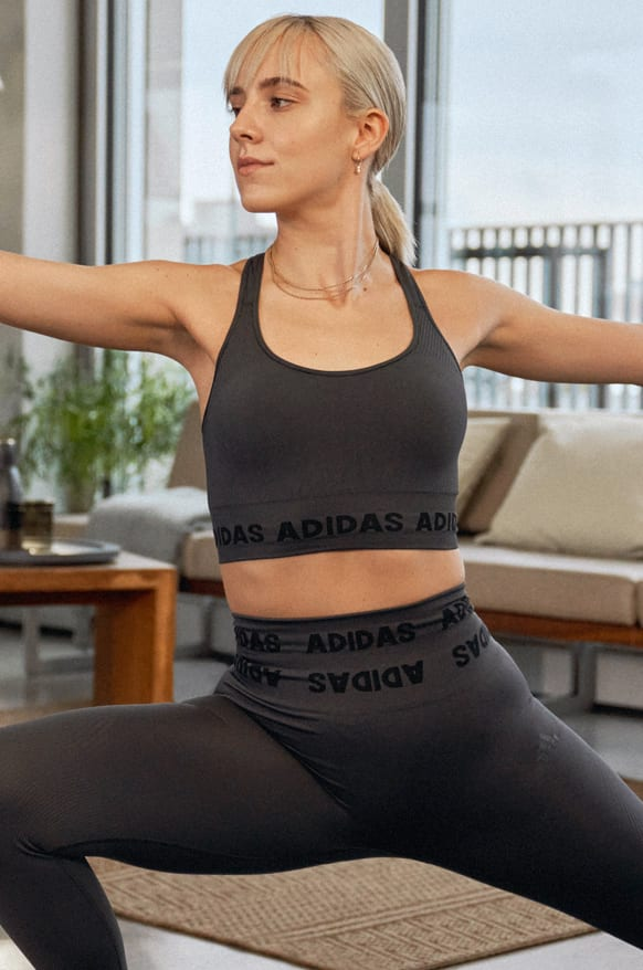 A woman in a black bra and tights in a standing yoga pose.