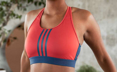 A close-up of a woman's chest, she is wearing a red and blue bra.