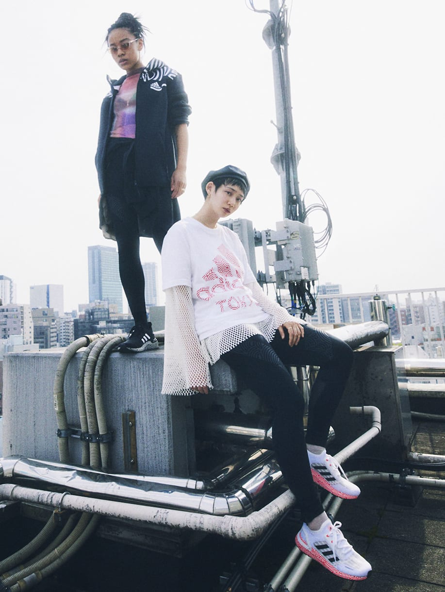 Two young women wearing items from HIROKO TAKAHASHI COLLECTION are standing on the rooftop overlooking Tokyo metropolis.