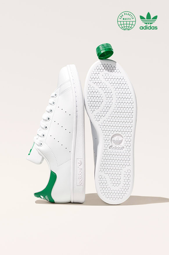 A pair of Stan Smith shoes with a bottle cap balanced on one toe.