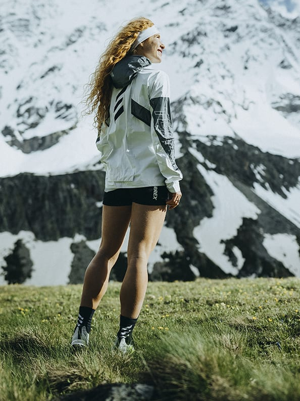 Athlete Ekaterina wearing the Agravic Ultra standing on trail in moutain landscape